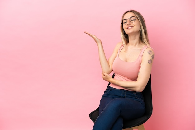 Young woman sitting on a chair over isolated pink background extending hands to the side for inviting to come
