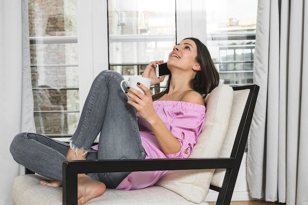 Young woman sitting on chair talking on mobile phone holding coffee cup in hand
