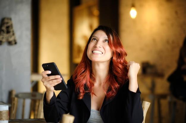 Молодая женщина сидит веселая держит свой мобильный телефон