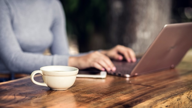 Young woman sitting in coffee shop at wooden table, drinking coffee and using laptop.