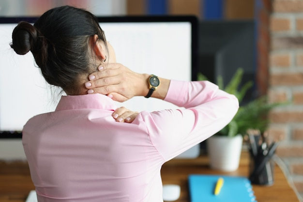 Young woman sitting at computer and holding her sore neck with her hand back view sedentary