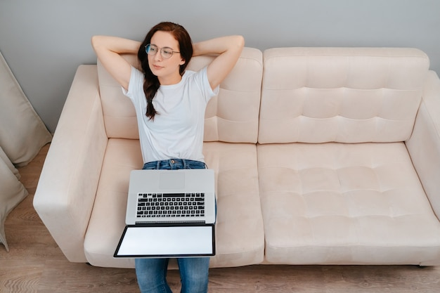 Young woman sitting on the couch at home is resting after finishing work on a laptop concept of free...