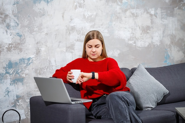 Young woman sitting on the couch looking at the laptop screen. a motivated, home-based female student freelancer working on a computer online.