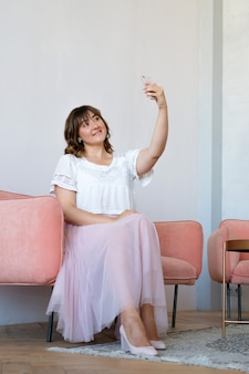 A young woman sitting on the couch in the room and takes a selfie on the phone