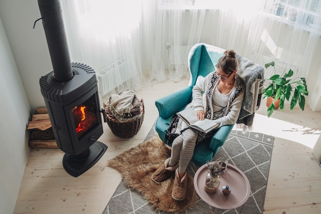Young woman sitting in a cozy armchair with a warm blanket reading a book
