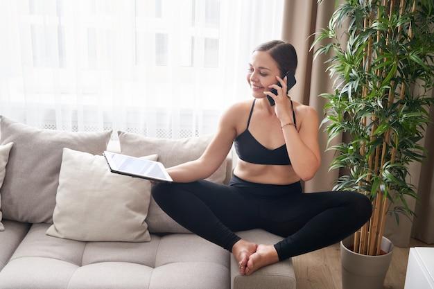 Молодая женщина, скрестив ноги, сидит на диване в позе лотоса, используя планшет и телефон дома в гостиной