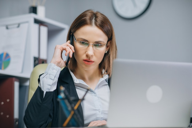 Young woman sitting at desk using laptop and talking on the phone