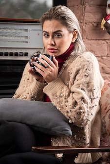Giovane donna seduta e bevendo un tè caldo