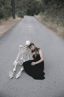 Young woman sitting on empty road in forest with skeleton