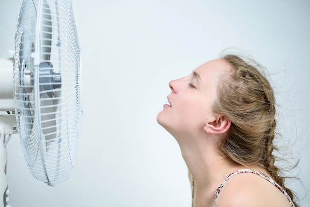 Young woman sitting under a fan with closed eyes from pleasure. summer heat.