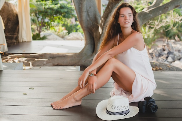 Young woman sitting on floor barefoot in pale dress, smiling, natural beauty, straw hat, digital camera,