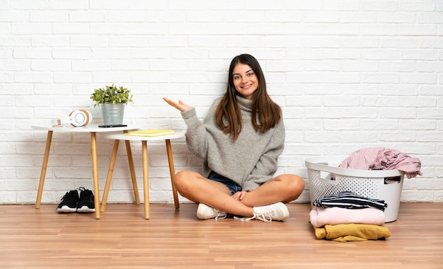 Young woman sitting on the floor at indoors with clothes basket extending hands to the side for inviting to come