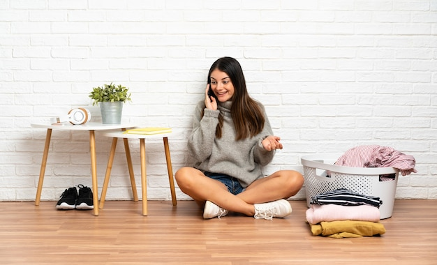 Young woman sitting on the floor at indoors with clothes basket keeping a conversation with the mobile phone with someone