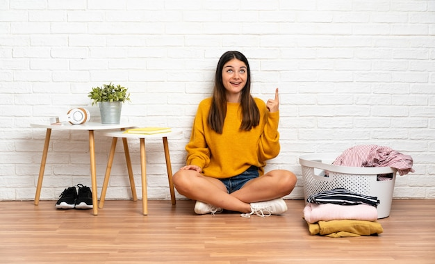 Young woman sitting on the floor at indoors with clothes basket pointing up and surprised