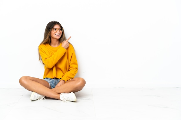 Young woman sitting on the floor isolated on white background pointing finger to the side