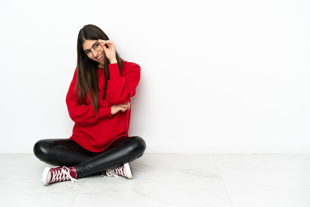 Young woman sitting on the floor isolated on white background with glasses and happy