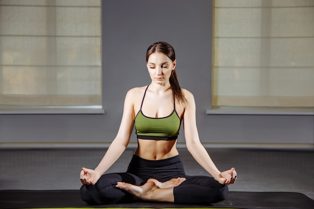 Young woman sitting on the floor in lotus position while meditating