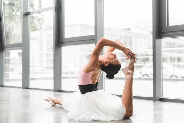 Young woman sitting on floor practicing ballet dance in dance studio
