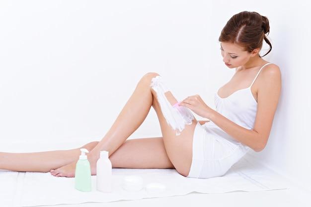 Giovane donna seduta sul pavimento e strofina le gambe
