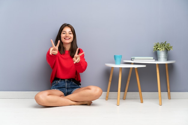 Young woman sitting on the floor smiling and showing victory sign