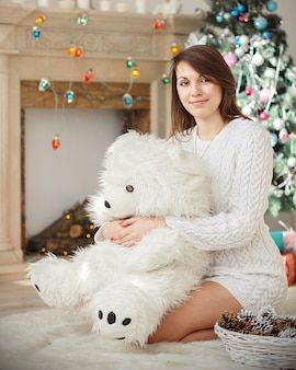 Young woman sitting on the floor in a sweater and hugs a big white teddy bear in christmas decorations