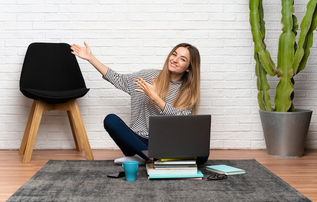 Young woman sitting on the floor with her laptop extending hands to the side for inviting to come