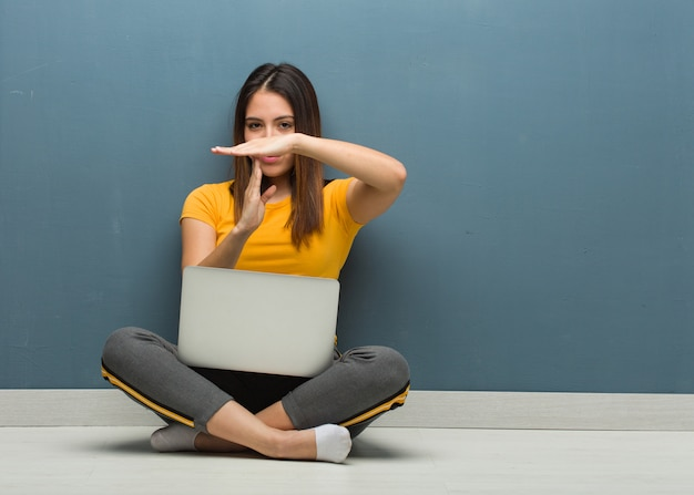 Young woman sitting on the floor with a laptop doing a timeout gesture