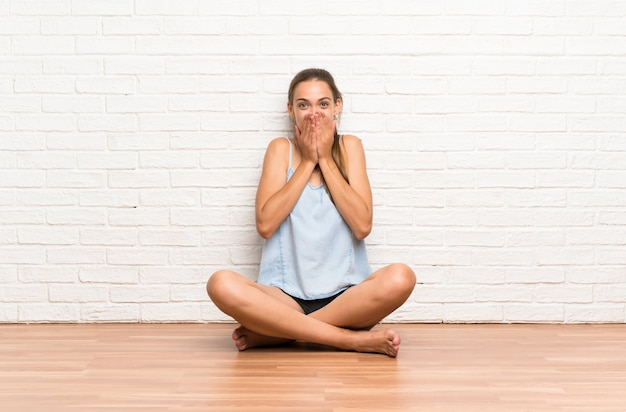 Young woman sitting on the floor with surprise facial expression