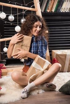 Giovane donna seduta su un soffice tappeto con scatole di regali di natale