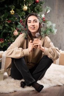 Una giovane donna seduta su un soffice tappeto con bacche di agrifoglio natalizio.