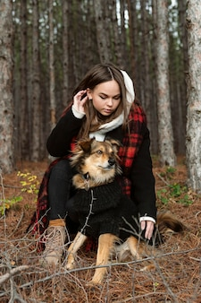 Young woman sitting in a forest with her dog