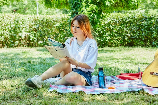 Young woman sitting on green grass while reading journal next to guitar