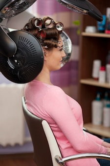Young woman sitting under hair dryer with rollers