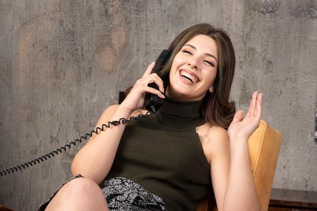 Giovane donna seduta felicemente sulla sedia e parlando
