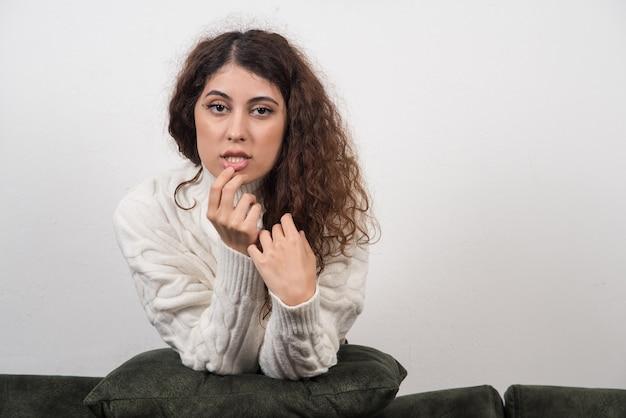 Una giovane donna seduta sul suo divano verde scuro con un cuscino in mano