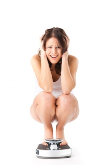 Young woman sitting on her haunches on a scale