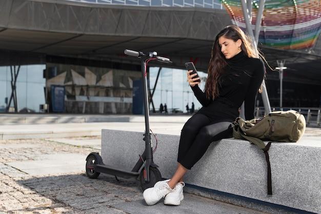 Giovane donna seduta accanto al suo scooter