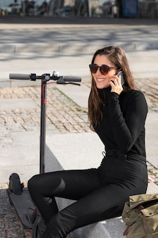 Young woman sitting next to her scooter