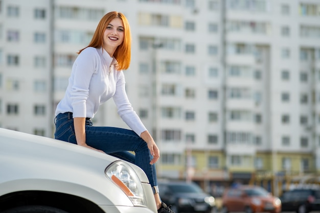 Young woman sitting on the hood of a car