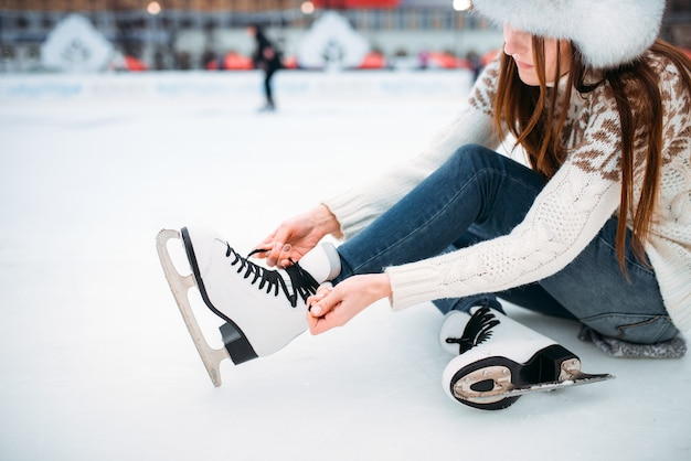 Young woman sitting on ice and ties the shoelaces on skates, skating rink. winter ice-skating on open air, active leisure
