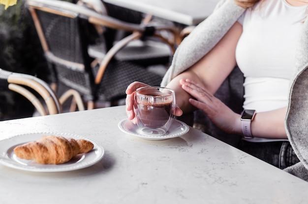 Молодая женщина, сидя в кафе утром и наслаждаясь горячим шоколадом и круассаном. фото