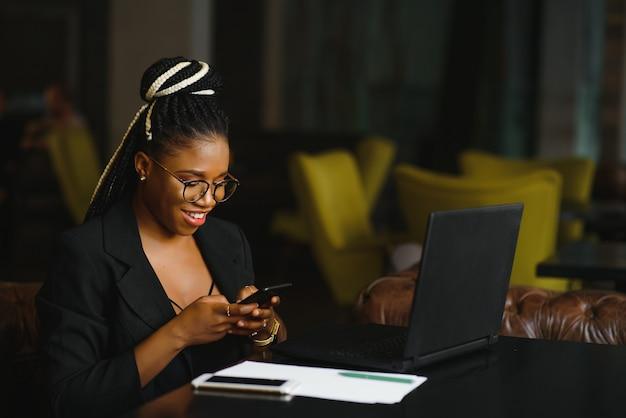 スマートフォンを使用してカフェに座っている若い女性