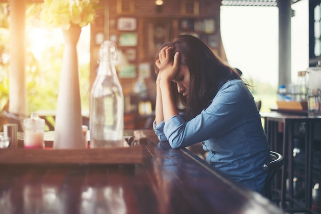 Молодая женщина, сидя в кафе с ее ноутбуком, стрессовым для вр