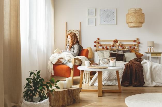 Молодая женщина, сидя в кресле с одеялом