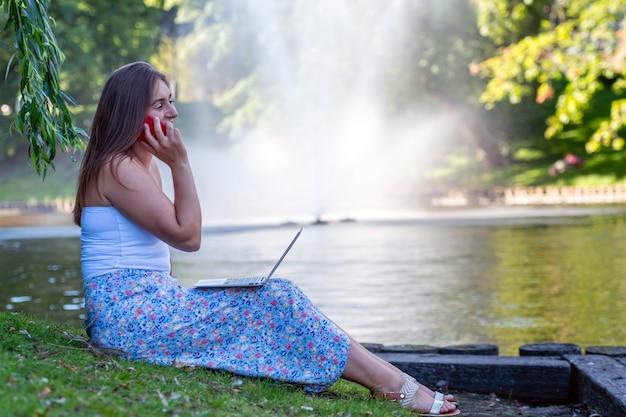 Молодая женщина сидит в городском парке у канала, разговаривает по телефону и работает на ноутбуке, дистанционное обучение и концепция работы