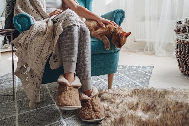 Молодая женщина, сидящая в уютном кресле, с теплым одеялом, вместе с домашней кошкой