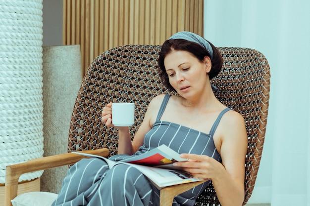 現代の肘掛け椅子に座っている若い女性