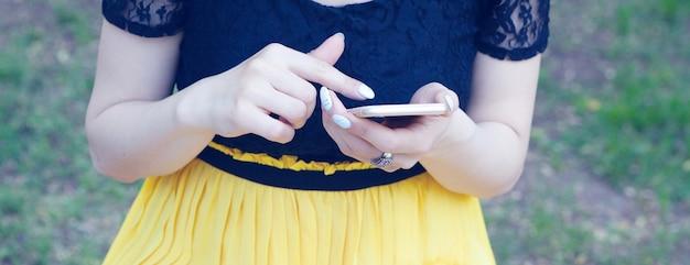 공원에서 전화에 앉아 젊은 여자