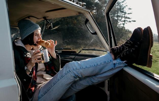 Молодая женщина, сидящая в фургоне с вытянутыми ногами