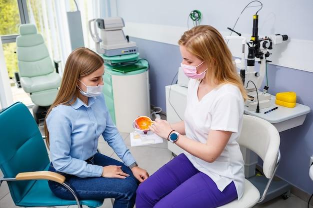 Молодая женщина, сидящая в кресле, глядя на щелевую лампу во время медицинского обследования в глазах